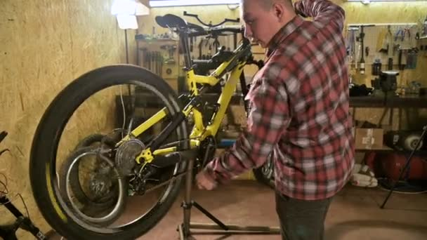 A bicycle technician repairs a mountain bike wheel on a bench in a bicycle  repair shop  Bicycle repair