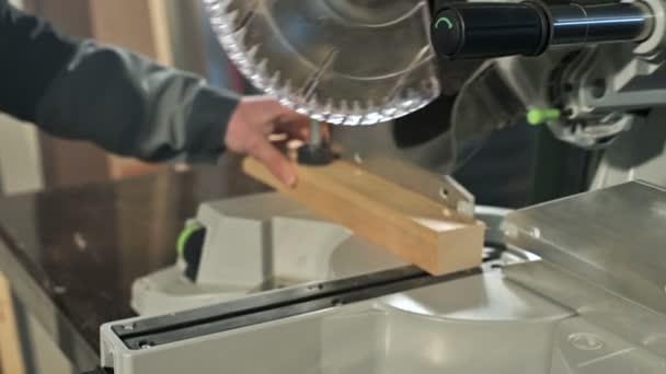 Close-up mans ruky pracující na stroji s kotoučovou pilou. Dřevěné sochory kruhové řezačky.