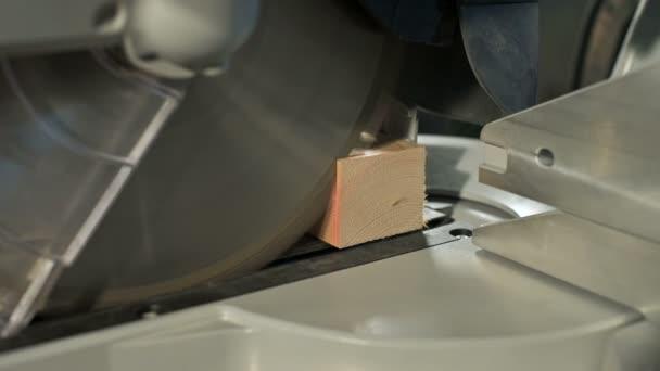 Close-up mans ruky pracující na stroji s kotoučovou pilou. Dřevěné sochory kruhové řezačky