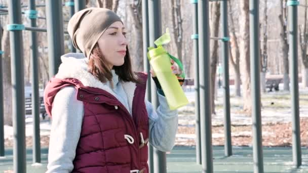 Sports girl at an outdoor workout in a park on the sports field in the winter on a sunny day drinking water from a shaker