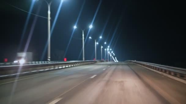 der Blick aus dem Auto durch die Windschutzscheibe des Autos auf der Nachtstrecke mit Beleuchtungslampen. Nachtautobahn