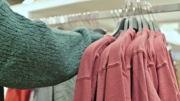 Detail dívky ruky v obchodě vybrat šaty na ramínka na prodej