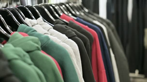 Close-up of multi-colored hoodies on hangers in a clothing store