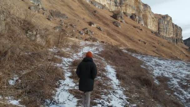 Girl tourist in a down jacket and hat walks along the path in early winter in a rocky gorge. yellow grass and pieces of snow on a sunny day. Aerial view