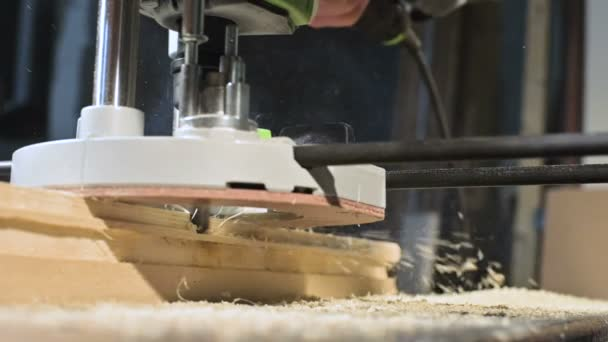 Close-up of a carpenters hand working with an manual electric cutter in a home workshop. Finishing wooden parts in slow motion