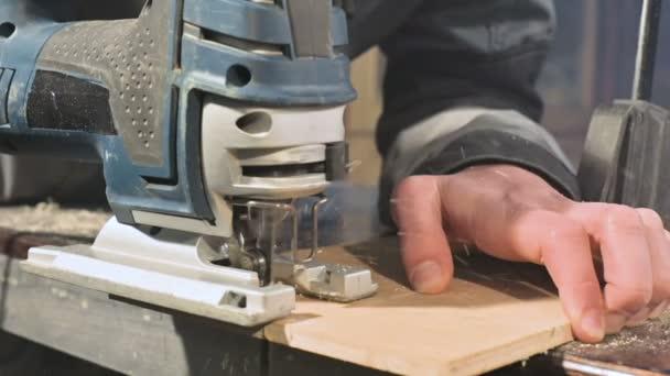 Mužští tesaři pracují jako elektrická skládačka v jeho domácí dílně. Pomalé řezání dřevěných částí