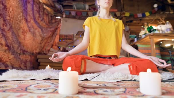 A beautiful young girl in loose clothes sits in a craft room on a white fur skin in a lotus position surrounded by candles. Meditation spiritual growth and care for your own health