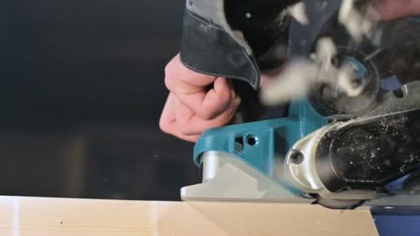 Uzavření truhlářské ruky pracující s elektrickým letadlem v domácí dílně. Pomalý pohyb v dřevěných dílech
