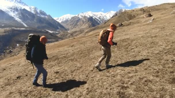 Two tourists photographers with backpacks in hats and sunglasses go up the hill on the yellow grass with cameras in their hands against the background of snowy mountains. slow motion
