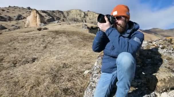 Portrét vousatého cestovatele fotografa v slunečních brýlích a čepici sedí na skále s zrcadlovou kamerou v dlaních a fotím na pozadí hor