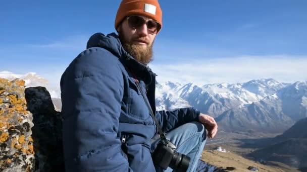 Portrét vousatého cestovatele fotografa v brýlích a Čapka sedí na skále s zrcadlovou kamerou v dlaních na pozadí hor