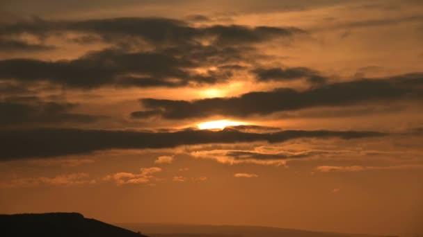 Superzoom plán, který prochází západem slunce skrze mraky slunce v oranžovém tónu. Nízká klávesa