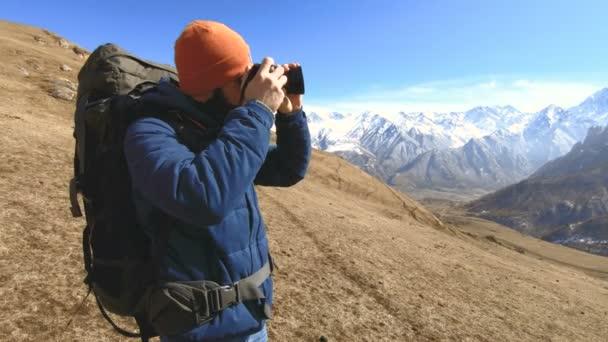 Portrét šťastného vousatého cestovatele fotografa v brýlích a klobouk s reflexní kamerou v dlaních a fotografování na pozadí hor. Koncepce cestování fotografií