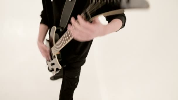 Stylish rhythm guitarist with different eyes in black clothes on a white background expressively playing the black guitar in a white studio