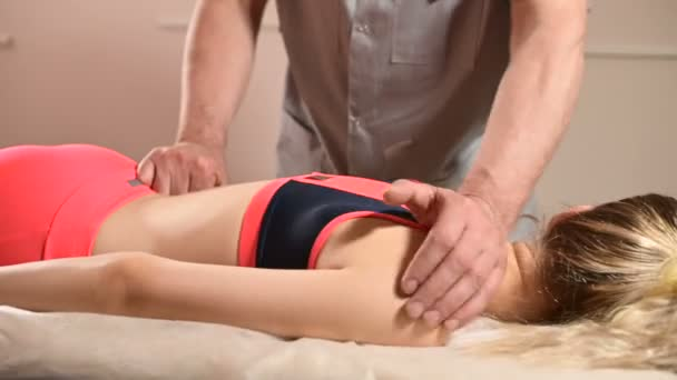 Close-up of a young girls spine base editing by a male physiotherapist of visceral massage. The hands of the doctor set and knead the tailbone of the patient