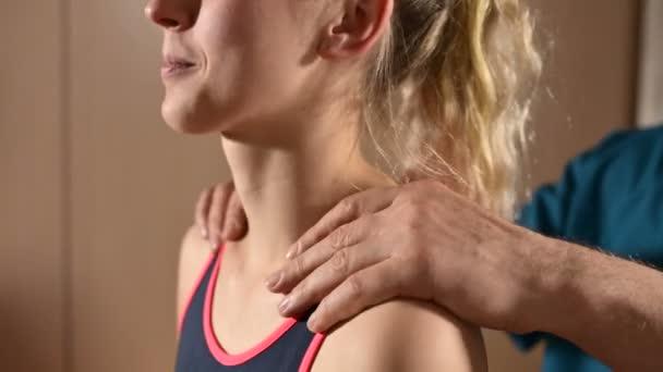 Samičí manuální terapeut, masér se chová jako mladá pacientka. Zahřátí ramen a krku