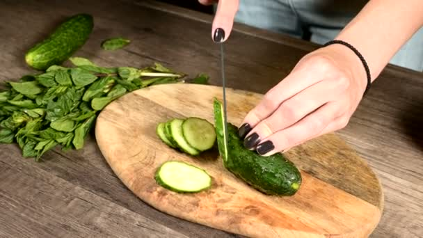 Close-up of female hands slicing cucumbers on a stroller on a cutting board next to chopped mint leaves. Healthy and Healthy Vegetarian Food