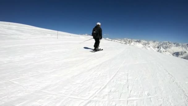 A wide angle male skier aged in black equipment and white helmet with ski poles rides on a snowy slope on a sunny day. The concept of winter ski sports
