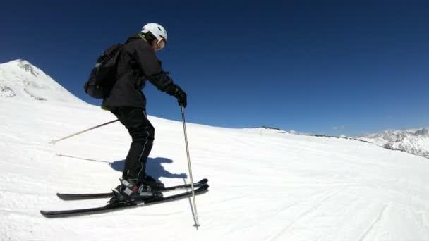 Ein Weitwinkelskiläufer in schwarzer Ausrüstung und weißem Helm mit Skistöcken fährt an einem sonnigen Tag auf einem schneebedeckten Hang. das Konzept des Wintersports