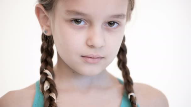 Close-up open look of a Caucasian girl with a pigtails opening and closing her eyes. Angry and blind in the camera