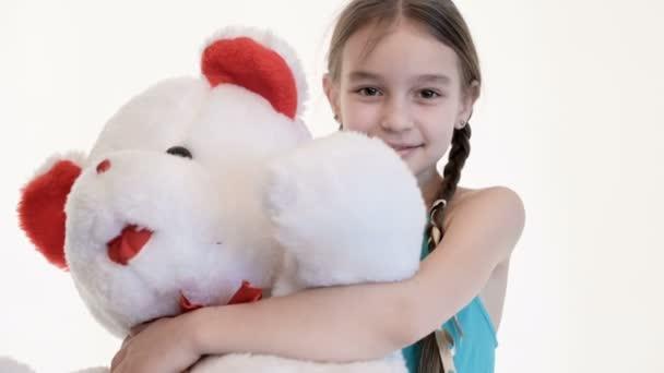 Portré egy aranyos fehér lány Pigtailek átölelve egy nagy mackó egy fehér háttér a stúdióban