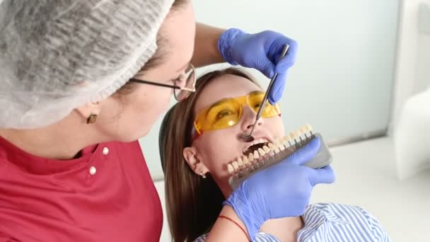 Pretty blonde girl in protective yellow glasses on the stamotologist examined her open mouth. Female dentist examines the oral cavity of a young patient with the help of a dentist instrument