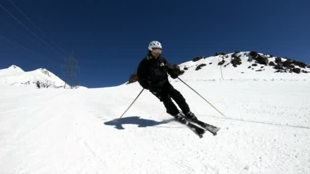 Široký, mužský lyžař v černém vybavení a bílá přilba s lyžařskými póly, jezdí za slunečného dne na zasněženém svahu. Koncept zimních lyžařských sportů