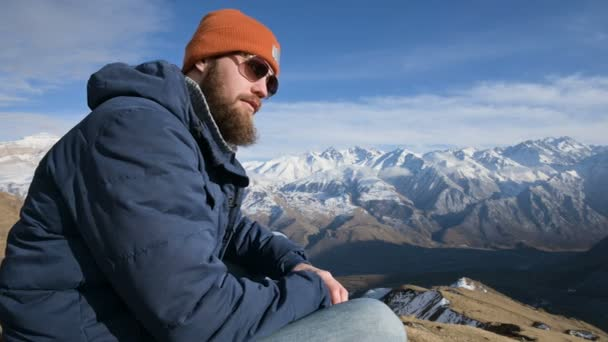 Portrait of a bearded traveler in sunglasses and a cap sits on a rock against the backdrop of mountains