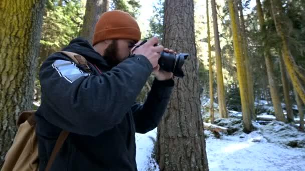 A szakállas férfi utazó fotós a kamerával a téli erdőben vesz képeket a természet. A bloggerek és a Fotóművészek utazási koncepciója