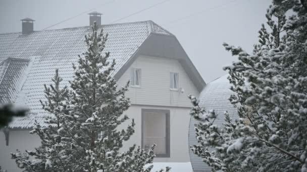 Gästehaus im Schneefall im Winter im Nadelwald. weicher, verschneiter Weihnachtsmorgen mit fallendem Schnee in Zeitlupe. Video-Hintergrund