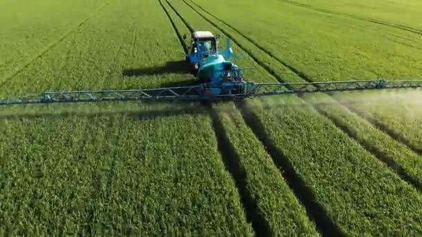 Letecký pohled na traktor, který zavlažuje zelené pole speciálním zařízením. Proces postřiku pesticidů a ochranou proti hmyzu hlodavců, parazitů a škůdců.