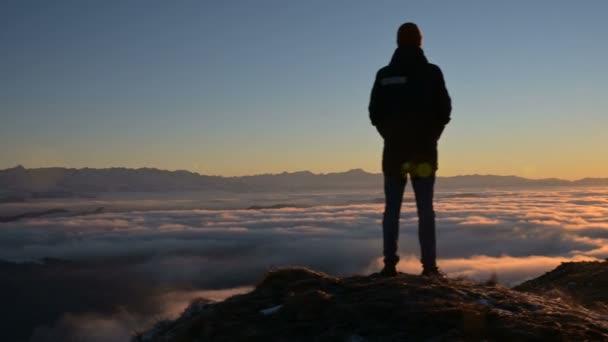 A sziluettje egy férfi áll naplemente felett a felhők, és szemléli a lenyugvó nap. A nyugalom és a kedvtelési célú utazás fogalma