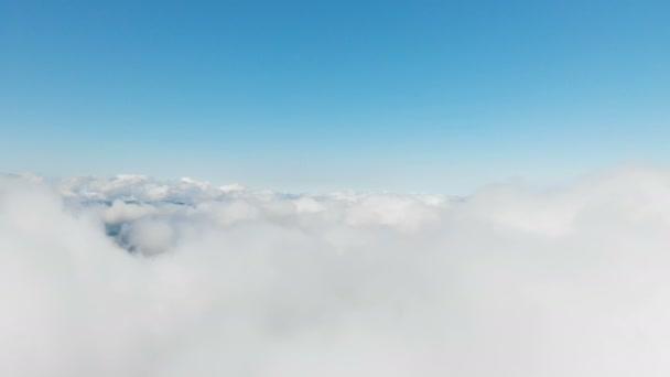 Letecký výhled na den nad a skrz mraky a kopce v horách za slunečného dne. Pojetí denních letů v horách oblačné pozadí