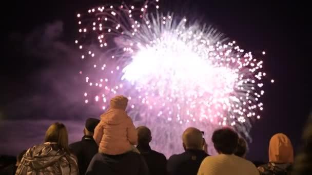 Noční rám za davem lidí, kteří sledují ohňostroj. Lidé na prázdninách sledují pyrotechnický výkon.