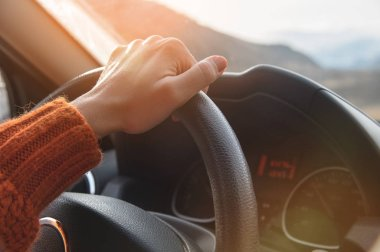 Close-up of a female hand in an orange sweater driving a car outside the city. Slow motion Woman driving a car