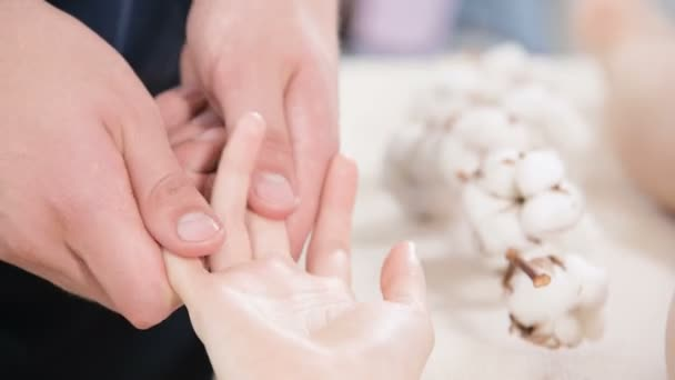 Blízcí mužští fyzioterapeuti dělají prstem a palmovu mladou dívku v masážním lázeňském salónu. Profesionální rozmazlování a hluboké relaxace
