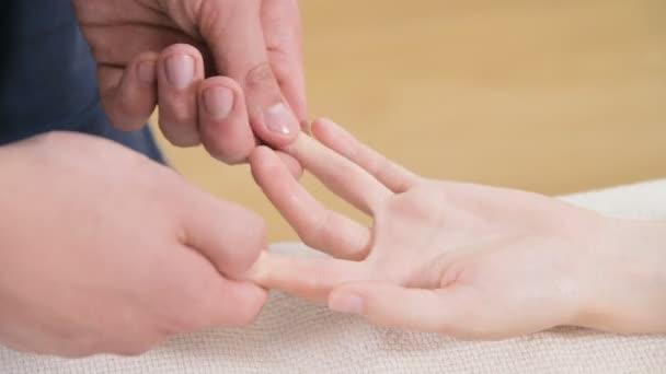 Közeli fel egy férfi gyógytornász csinál ujj-és pálmamasszázs egy fiatal lány egy masszázs Spa szalon. Professzionális kényeztetés és mély relaxáció