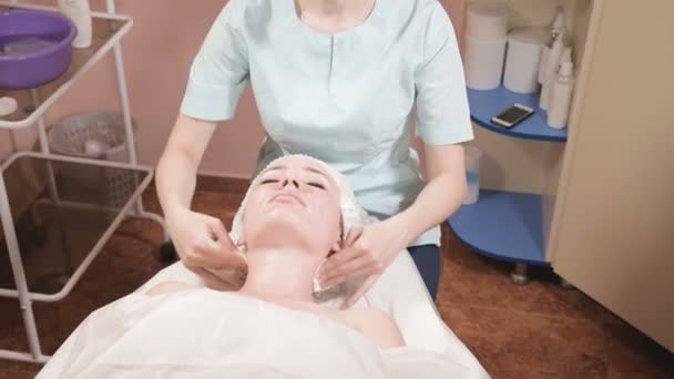 Girl beautician in a mask and gloves makes a salubrious facial massage to an attractive woman. New generation cosmetology massage