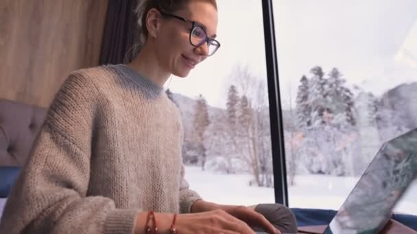 Portrait of attractive freelancer woman with glasses and a sweater with stockings sitting on a bed in an eco-house in the middle of a winter forest with a laptop