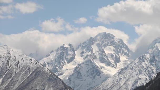 4k video timelapse vysoké strmé hory kavkazského sněhu s ledovci a plovoucí na nich mraky a modré nebe.