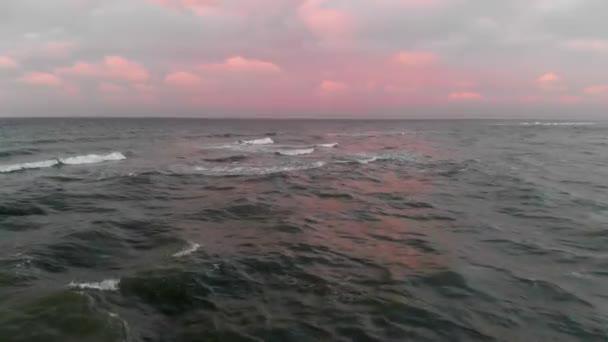 Eine Luftaufnahme des Fluges über der Ostseeküste am Abend kurz nach Sonnenuntergang. Konzept eines Videos über den Hintergrund des Meeres aus der Vogelperspektive rosa Wolken am Himmel