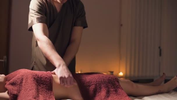 Zblízka mělká hloubka pole. Profesionální elitní masáž břišní anti-celulitidy a užitečná pro vnitřní orgány v tmavé masážní místnosti