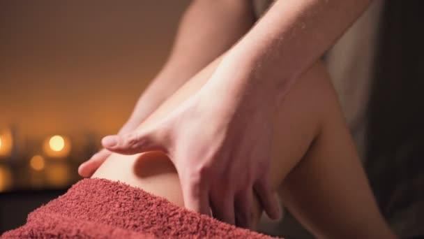 Detailní profesionální masáž kyčle v lázeňském salonu s příjemným teplým světlem. Mužský masér provádí prémiovou masáž klientce. Boj proti celulitidě a profesionální péči o tělo a pokožku