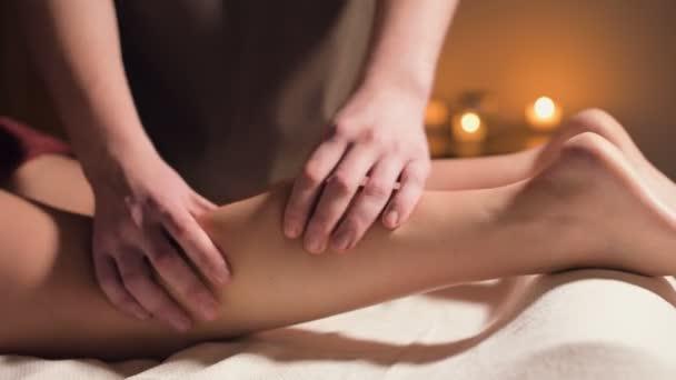 Nahaufnahme der Handmassage des Wadenmuskels. Eine professionelle Massagetherapeutin massiert ein Frauenbein in einem Büro mit schönem Licht
