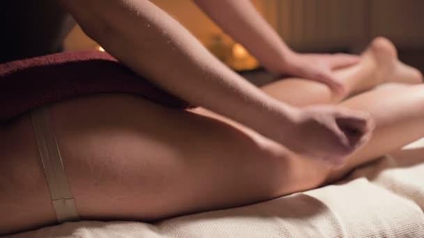 Közelkép professzionális csípőmasszázs a spa szalonban egy kellemes meleg fény. Egy férfi masszőr prémium masszázst végez egy női ügyfélnek. Küzdelem a cellulit és a szakmai szervezet és a bőrápolás ellen