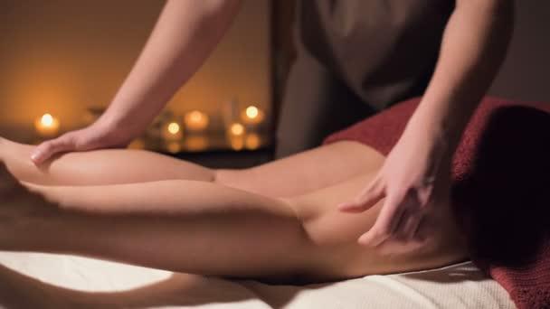 Detailní profesionální masáž ženského kyčle v tmavém pokoji lázeňského salonu na pozadí hořících svíček. Koncept zdraví kyčelního svalu