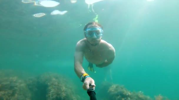 Ein Selfie, aufgenommen unter Wasser von einem kaukasischen Mann mit Körperbau, schwimmt wunderschön unter Wasser. Das Konzept des freien Tauchens und der Erholung an der Küste oder auf dem Ozean