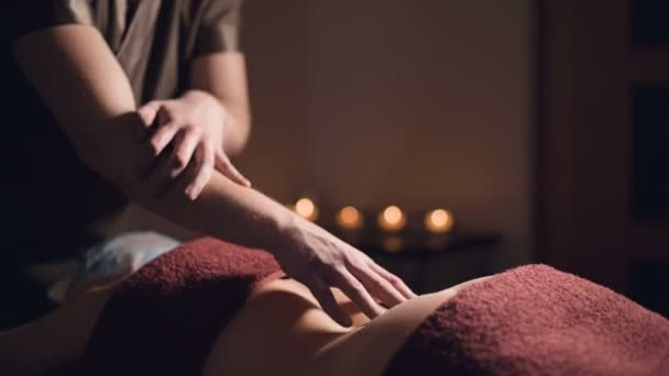 close-up Kosmetologie a fyzioterapie. Profesionální masáž do dolní části zad ženy provádí masér. Koncepce manuální terapie a masážní lázeňské léčby