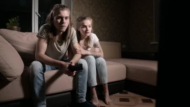 Mladý pár a dívka v napětí sledovat televizi se sportovními soutěžemi pozdě v noci nebo v noci. Koncept společného volného času v mladých rodinách