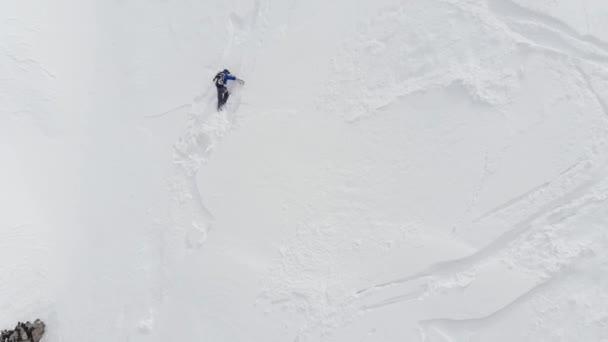 Vzdušný pohled na mužského sportovce, který se škrábe na strmý svah. Skitour freeride backcountry lezení s lyžemi přes sníh vysoko v horách severního Kavkazu